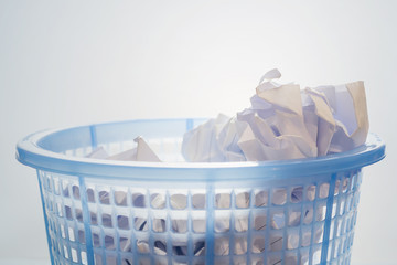 Closeup, Blue mesh waste bin filled of white paper against gradient background.