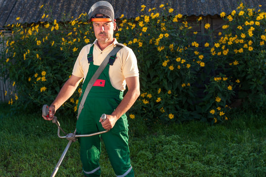 The gardener in the green overalls holds a lawn mower in his hands. Gardening at sunset