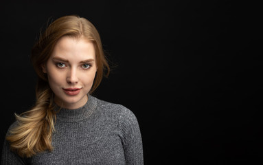 portrait of blonde girl on dark background