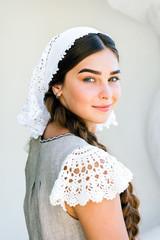 Russian beauty, a girl in a white lace dress, a long braid, a headdress