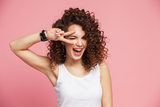 Image of happy young woman standing isolated over pink background showing peace gesture. Looking camera