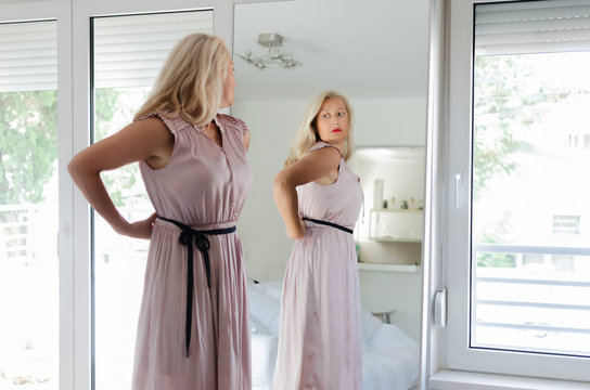 Woman standing in dress in front of mirror