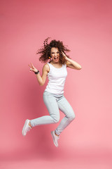 Full length portrait of a joyful young woman jumping and celebrating over pink background.