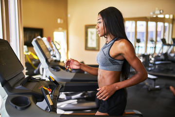 fit african american woman running on treadmill at gym