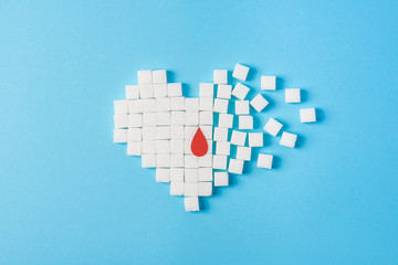a drop of blood on broken heart made of pure white cubes of sugar isolated on blue background, World diabetes day