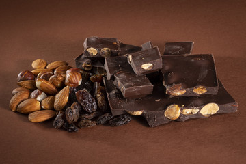 Stack of dark chocolate pieces with roasted almonds and raisins