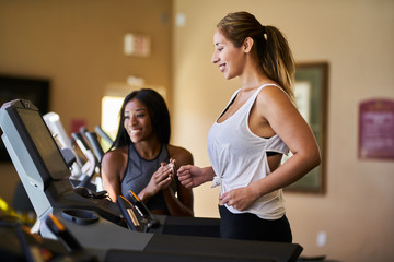 personal trainer teaching woman how to use treadmill in gym