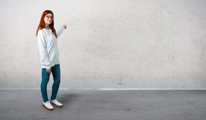 Young redhead girl in an urban white sweatshirt with glasses pointing back with the index finger presenting a product and standing on a vintage gray wall