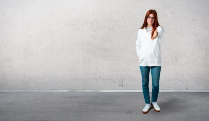 Young redhead girl in an urban white sweatshirt with glasses shaking hands for closing a good deal and standing on a vintage gray wall