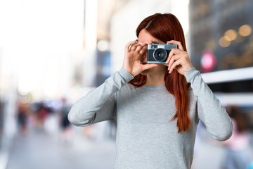 Young redhead girl holding a camera on unfocused background