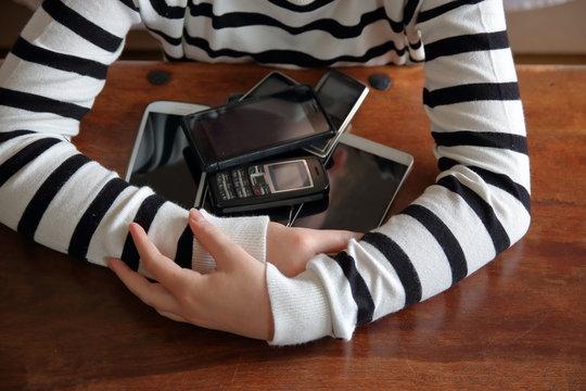 Ręce dziewczynki ubranej w pasiasty sweterek otaczają stos różnych telefonów komórkowych i smartfonów, wszystko to leży na drewnianym stole, dziewczynka jakby przyciągała do siebie te urządzenia