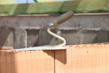 bricklaying trowel on a brick wall