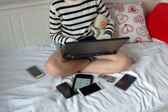 Dziewczynka w pasiastym sweterku, z gołymi nogami, siedzi na sofie, na kolanach ma otwartego czarnego laptopa, obok niej leżą porozrzucane smartfony, przytula pluszową kaczkę, w pokoju