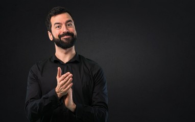 Handsome man with beard applauding on black background