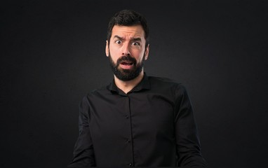 Handsome man with beard stressed overwhelmed on black background