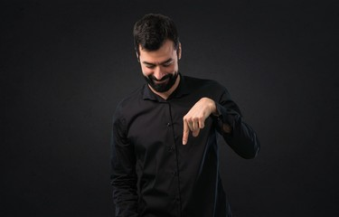 Handsome man with beard pointing down on black background