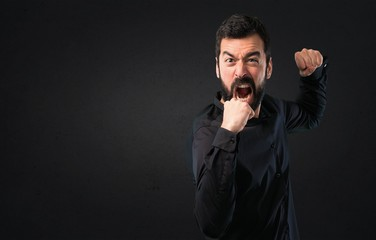 Handsome man with beard fighting on black background