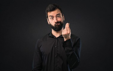 Handsome man with beard making money gesture on black background