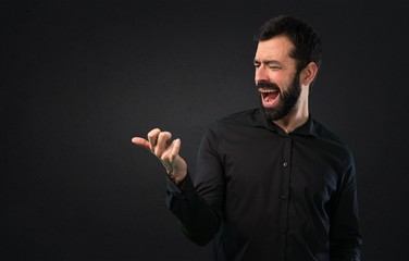 Handsome man with beard making guitar gesture on black background