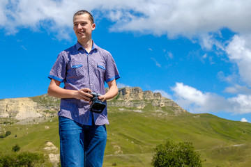 A young man in a blue shirt photographs mountains.