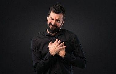 Handsome man with beard with heart pain on black background