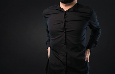 Handsome man with beard with back pain on black background