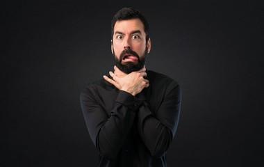 Handsome man with beard drowning himself on black background
