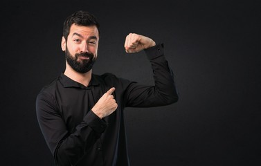 Handsome man with beard making strong gesture on black background