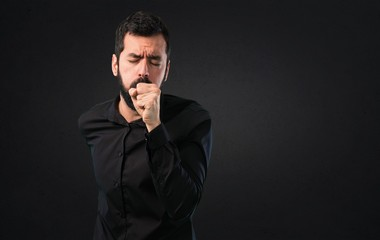 Handsome man with beard coughing a lot on black background