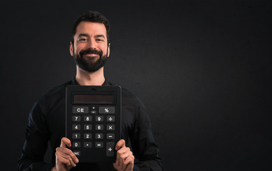 Handsome man with beard holding a calculator on black background