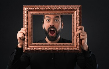 Handsome man with beard holding a framework on black background
