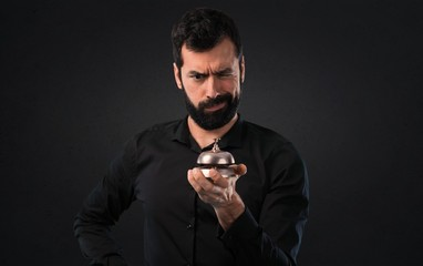 Handsome man with beard with ringbell on black background