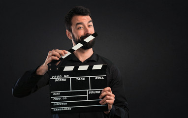Handsome man with beard holding a clapperboard on black background
