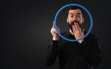 Handsome man with beard looking through an circle frame on black background