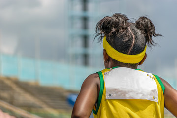 Young black female child athlete wearing yellow and green jersey and headband in outdoor track and field stadium
