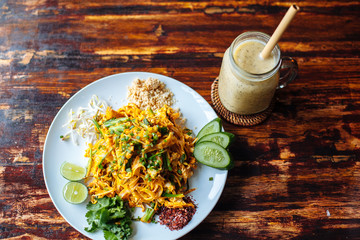 Healthy Vegetarian vegan menu Pad Thai, stir-fried rice noodles, is one of Thailand's national main dish and banana smoothies on wooden table.top view