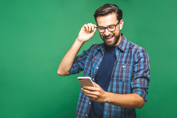 Always in touch. Smiling young man holding smart phone and looking at it. Portrait of a happy man using mobile phone isolated over green background. Wall mural