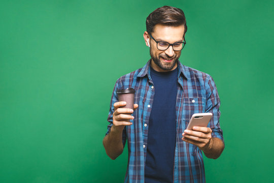 Portrait of happy young man talking on phone and drinking tea. Isolated over green background.