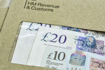England, UK - August 16 2018: The logo of Her Majestys Revenue and Customs on envelope, with money or check included inside.  HMRC is a non-ministerial dept of the UK Government. Editorial only.