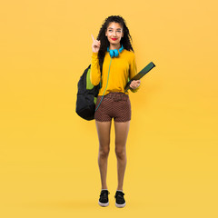 Full body of Teenager student girl with curly hair standing and thinking an idea pointing the finger up on yellow background