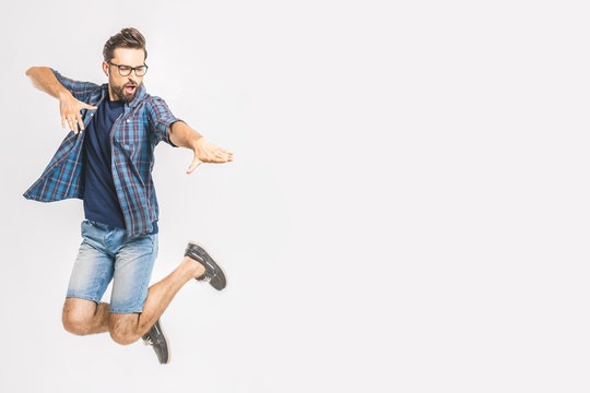 Happy excited cheerful young man jumping and celebrating success isolated on a white background