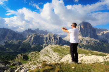 Man takes pictures with his cell phone to the mountain landscape of the Alpine peaks.