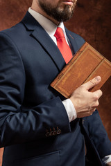 Man in suit stands with old vintage book