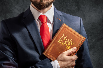 Man looks like politician or businessman stands with holy bible
