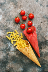 Pasta and tomatoes in multi-colored waffle cones on a rustic background. Top view, overhead, flat lay.