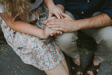 Couple in park holding hands with rings