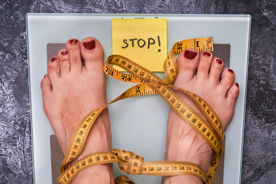 Stop Anorexia nervosa! Society perception, pressure about weight problem. Skinny female feet on a scale with yellow measuring tape. Loss weight social stigma. Body  positive concept.