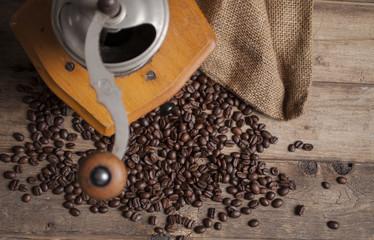 Kaffeebohnen mit Kaffeemühle auf rustikalem Holz mit Jutesack