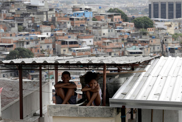 Kids are pictured on the roof of their house in Sao Carlos slums complex in Rio de Janeiro