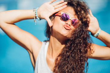 Portrait of fashionable long curly dark hair lady making selfie posing beside exotic summer beach hot summer. go crazy